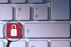composite of padlock symbol on keyboard with magnifying glass